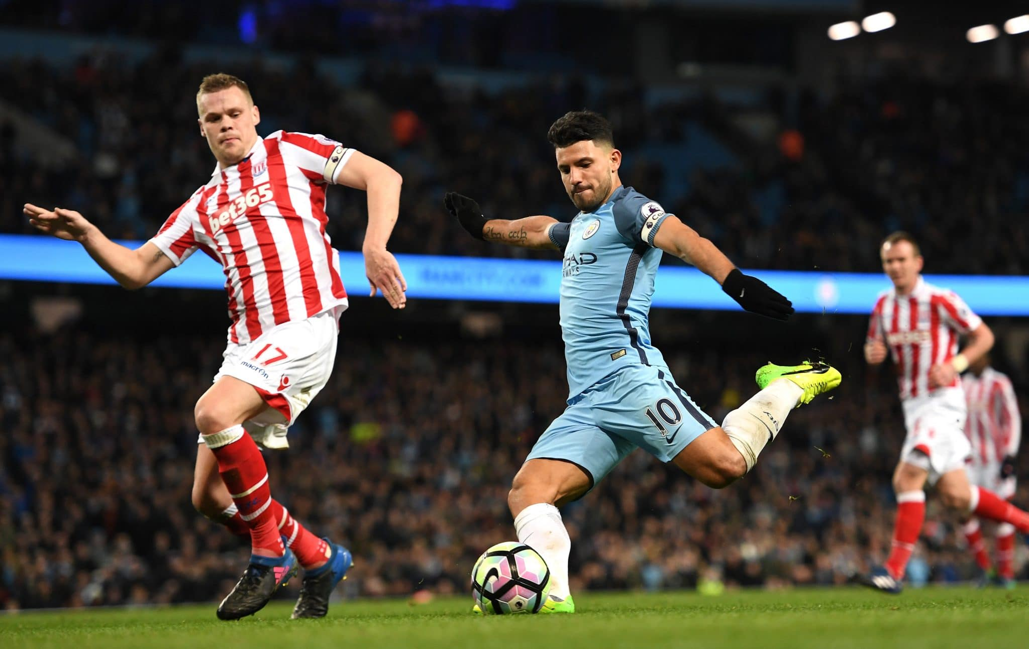 Manchester City striker Sergio Aguero gets a shot off against Stoke City defender Ryan Shawcross