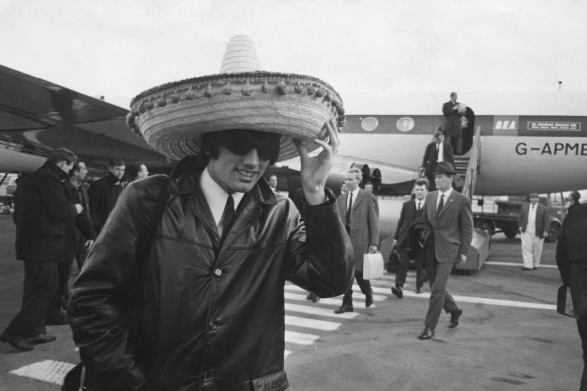 Manchester United footballer George Best (1946 - 2005) arrives back at London Airport wearing a large sombrero, after his team's 5-1 victory over Benfica in a European Cup match in Lisbon