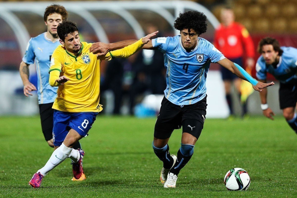 Boschilia of Brazil and Mauricio Lemos of Uruguay compete for the ball during the FIFA U-20 World Cup New Zealand 2015